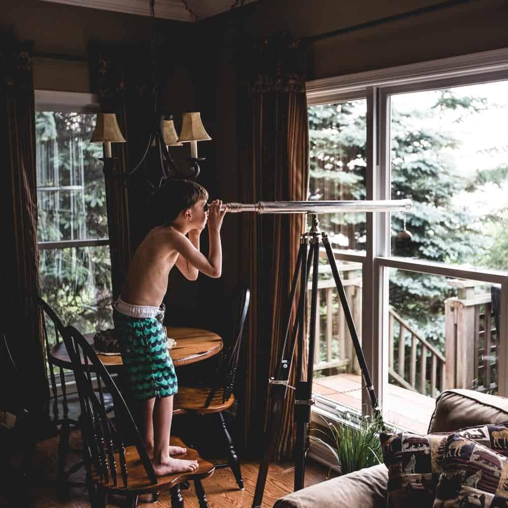kid using a heavy telescope instead of a monocular