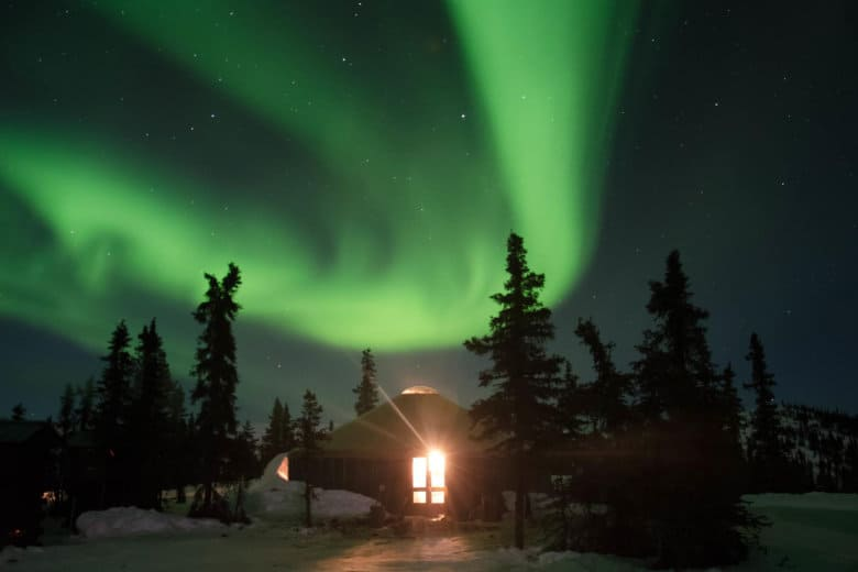 cabin with the northern lights in the sky