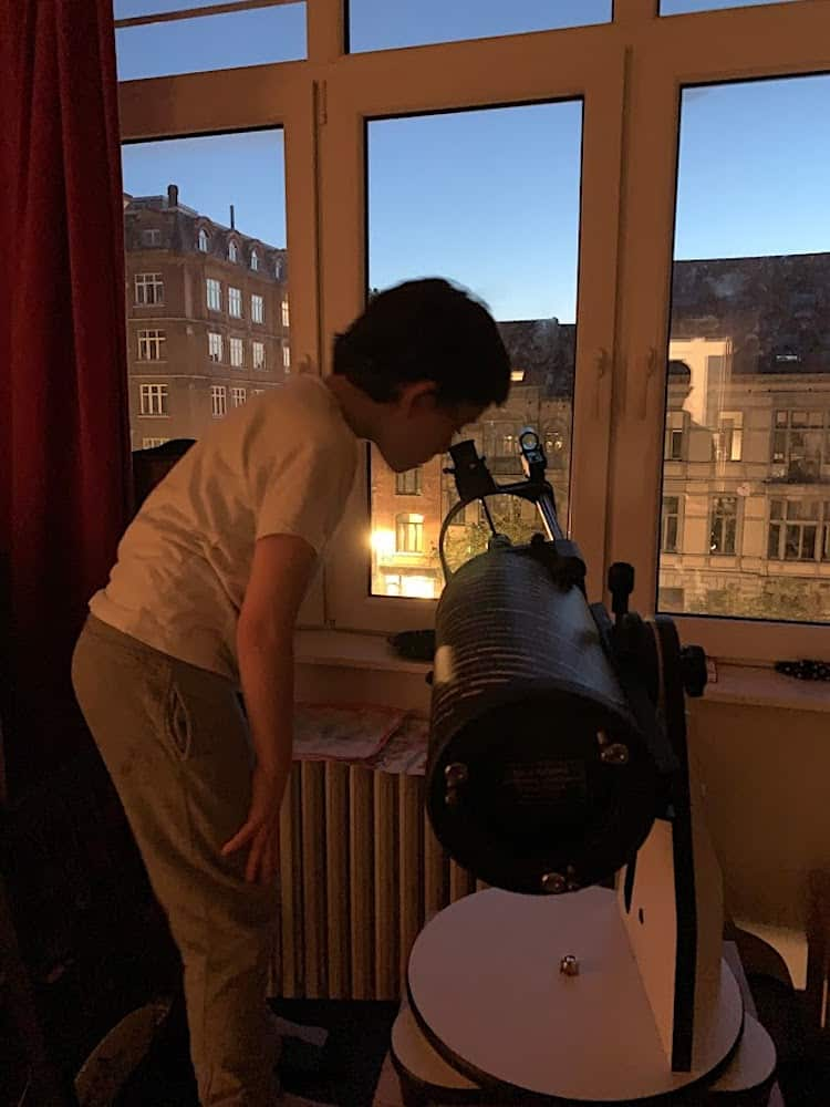 teenager looking through telescope to see Jupiter
