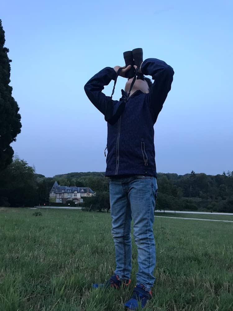 child using binoculars to view the moon on vacation