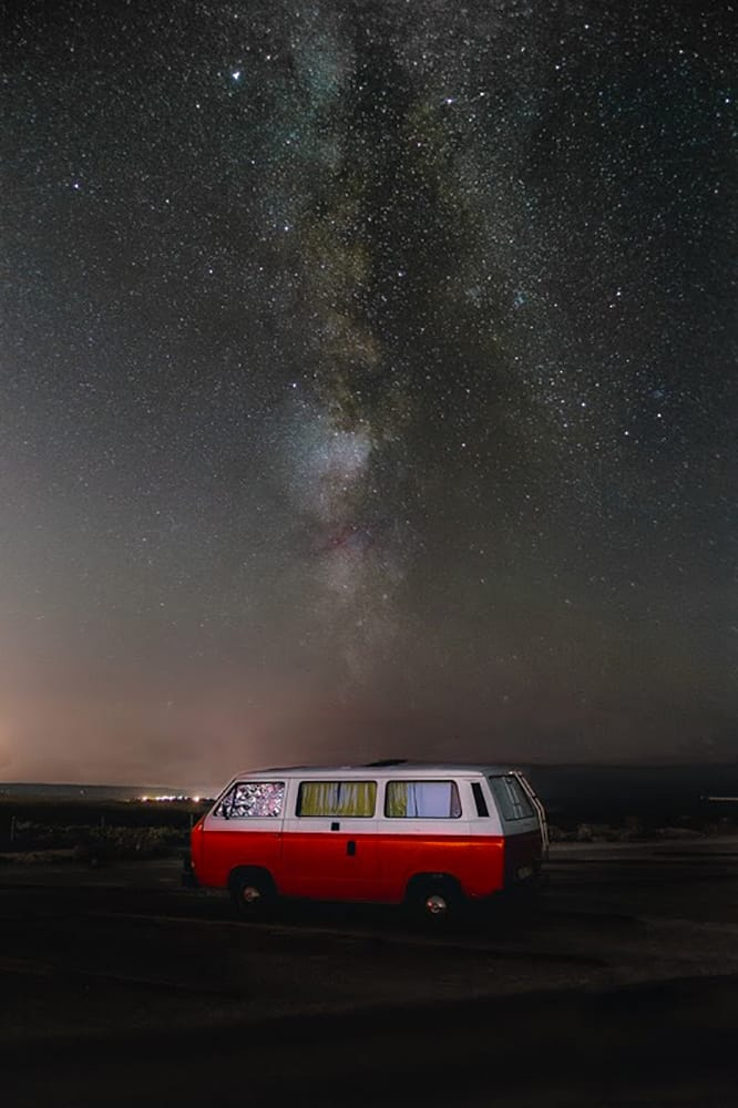 van parked with milkway in the sky