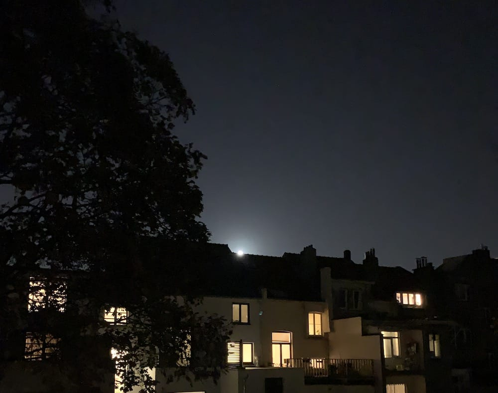 Moon is rising from behind some roofs