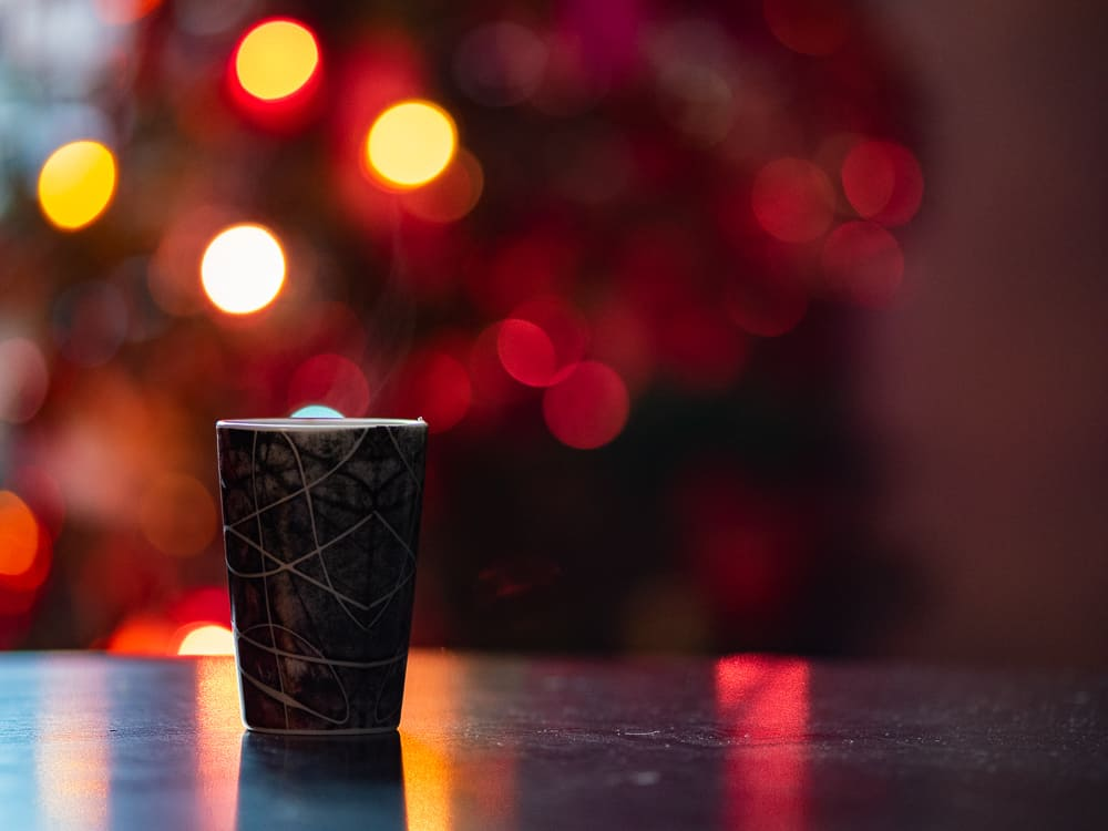 cup with bokeh effect blurring xmas tree lights