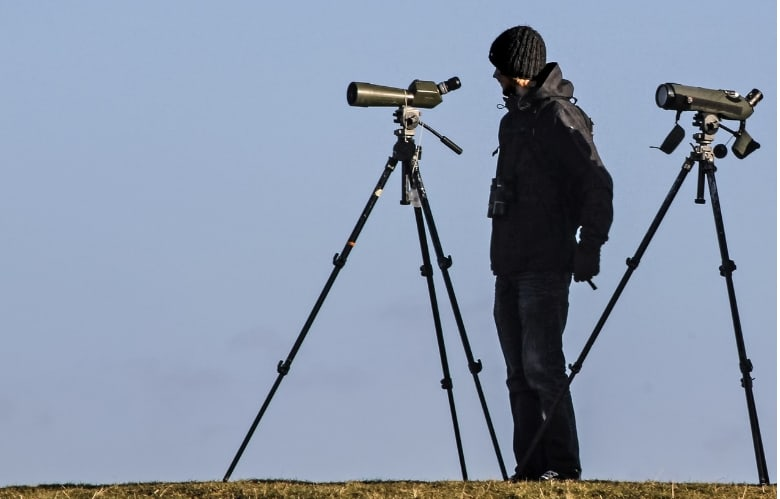 A man with spotting scopes attached to a tripod