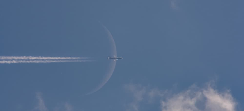A plane transiting in front of the crescent Moon