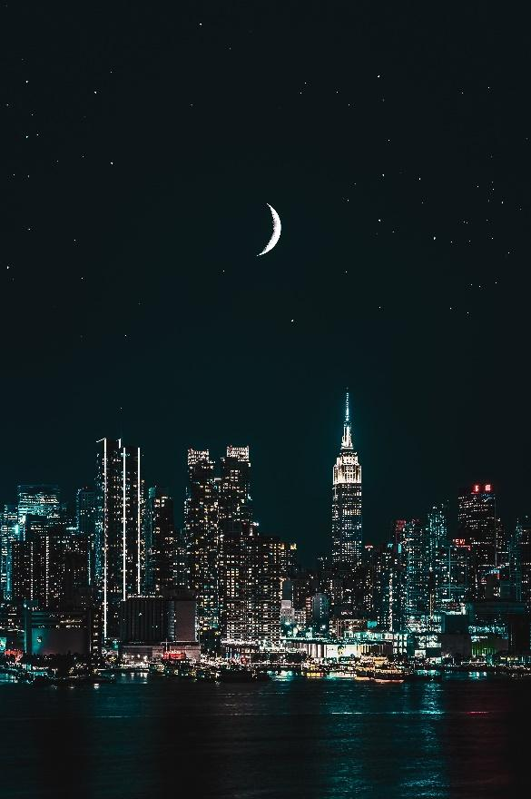 The moon shines brighter than the city lights.