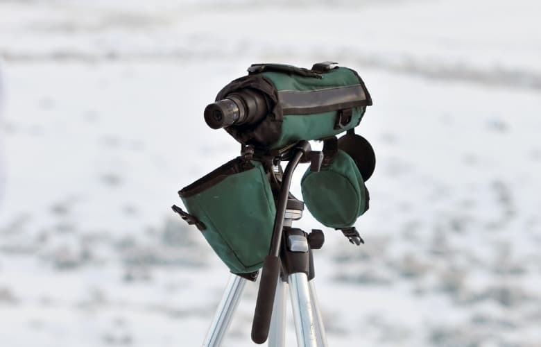 A monocular set up in the wilderness with cover to keep it safe